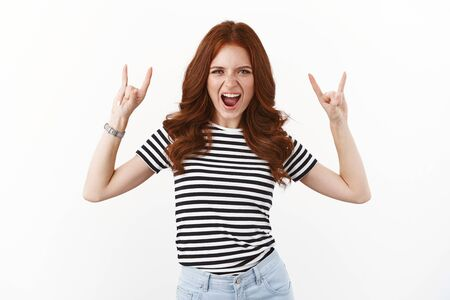 Wild and carefree good-looking redhead amused girl in striped t-shirt yelling excited, showing rock-n-roll, heavy metal gesture, open mouth enthusiastic and upbeat, enjoy awesome party