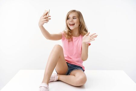 Foto de Cheerful enthusiastic happy blond teenage girl sitting crossed legs on floor, hold smartphone, record blog, communicate father abroad, taking selfie, waving hand greeting say hi mobile phone - Imagen libre de derechos