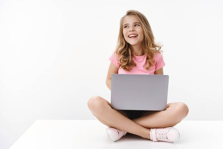 Foto de Carefree cheerful blond caucasian cute kid young sister sitting floor with laptop, laughing joyfully, studying online, digital education, look away left copyspace, smiling happy, learn new language - Imagen libre de derechos
