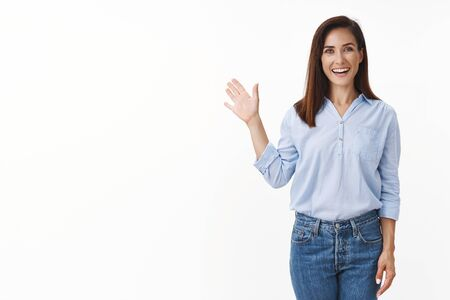 Friendly good-looking european woman entrepreneur with tattoo joyfully welcome you, wave palm gladly invite greet person, smiling broadly, enthusiastic grin, say hi hello, stand white background