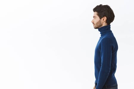 Foto de Profile shot serious-looking handsome businessman in blue high neck sweater, standing straight with determined, assertive expression, pose white background no emotions, dress-up for party - Imagen libre de derechos