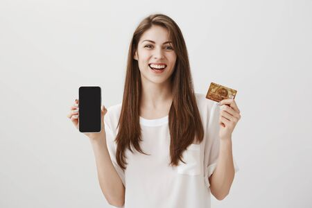 Photo pour Bought smartphone in credit and proud of it. Studio shot of emotive happy young female student showing bank card and new phone, bragging about new purchase and positive bonuses from banking system - image libre de droit