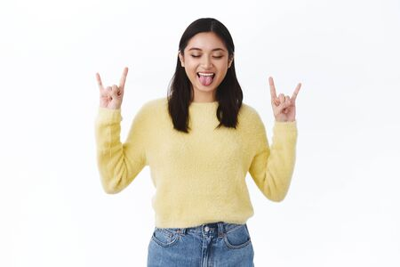 Wild and free millennials. Gorgeous carefree asian girl in yellow sweater, having fun at awesome student party, close eyes show tongue and smiling, make rock n roll gesture to express excitement
