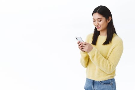 Photo pour Happy cute asian girl using mobile phone and smiling. Female student sending funny meme via social media messanger, chat with friends or team members, video-call on smartphone, white background - image libre de droit