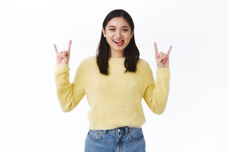 Lets rock this party. Beautiful excited asian girl having fun on awesome concert, making rock-n-roll gesture and showing tongue as smiling carefree, dancing to cool music, standing white background