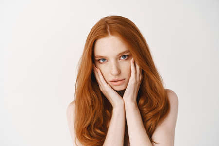 Photo for Beauty. Close-up of natural young woman with ginger hair, touching pale clean no make-up face and looking at camera, standing naked over white background - Royalty Free Image