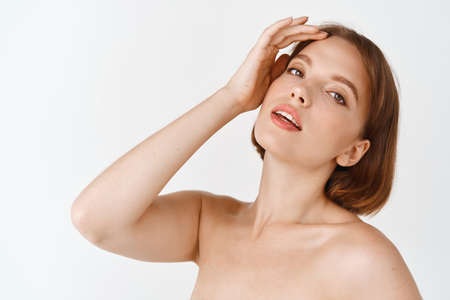 Photo pour Skin care beauty. Natural girl with naked shoulders and short hair, touching facial skin after daily-care product. Woman using cosmetics with detoxifying effect, white background - image libre de droit
