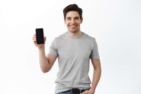Photo pour Caucasian handsome man show mobile phone screen, smiling and giving app recommendation, standing in t-shirt against white background - image libre de droit