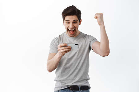 Photo pour Happy successful guy rejoicing, winning online, playing video game on smartphone, scream yes with satisfied face, standing against white background and celebrating - image libre de droit