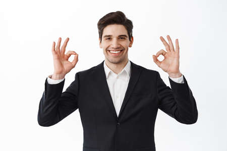 Photo pour Very good. Smiling satisfied businessman, male entrepreneur in business suit, show okay signs and nod in approval, say yes, agree and praise work, white background - image libre de droit