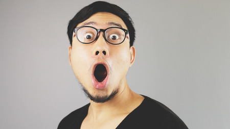 Shocked Asian man close up.の写真素材