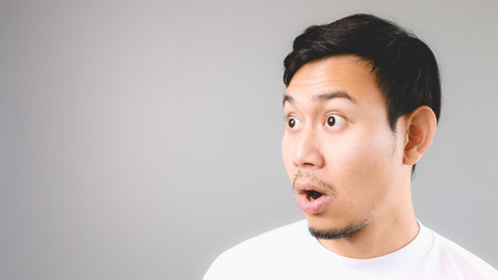 Surprise face on empty copyspace. An asian man with white t-shirt and grey background.