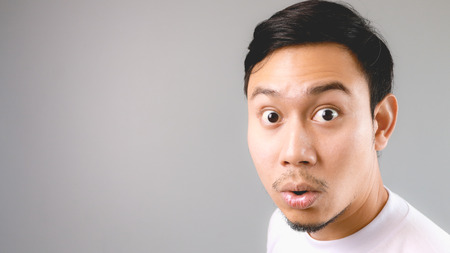 Wow, He is surprised to hear the news. An asian man with white t-shirt and grey background.
