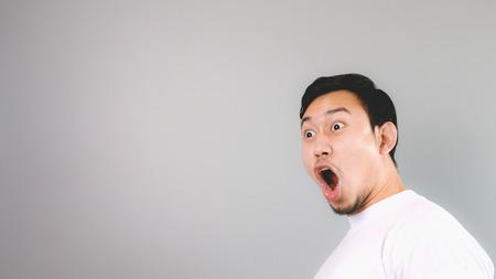 Photo pour Shock face on empty copyspace. An asian man with white t-shirt and grey background. - image libre de droit
