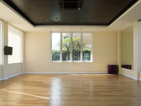Photo for Empty fitness room with yoga mat television and garden view windows. - Royalty Free Image