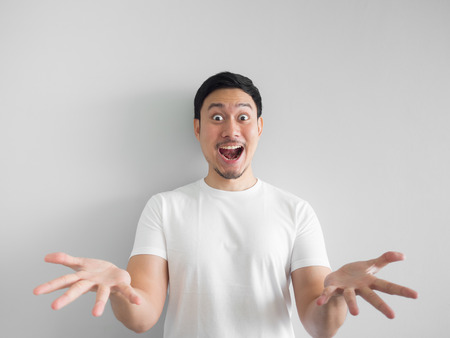Foto de Surprised face of happy asian man in white shirt  light grey background. - Imagen libre de derechos