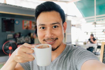 Foto de Selfie portrait of happy Asian man drink mug of hot coffee. - Imagen libre de derechos
