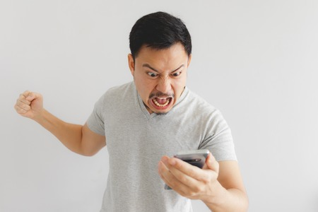 Photo pour Angry Asian man in grey t-shirt get mad on the smartphone. - image libre de droit