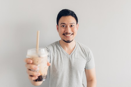 Photo for Happy Asian man is drinking Bubble Milk Tea or Pearl Milk Tea. Popular Milk Tea in Asia and Taiwan. - Royalty Free Image