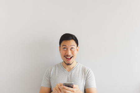 Photo for Wow face of Asian man in grey t-shirt get surprised on the smartphone. - Royalty Free Image