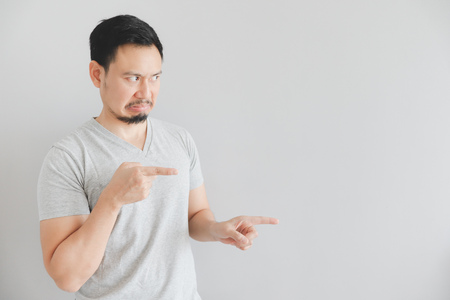 Photo pour Hate face of Asian man in grey t-shirt with hand point on empty space. - image libre de droit