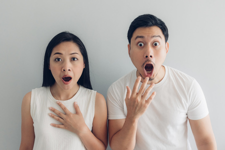 Photo pour Surprised and shocked Asian couple lover in white t-shirt and grey background. - image libre de droit