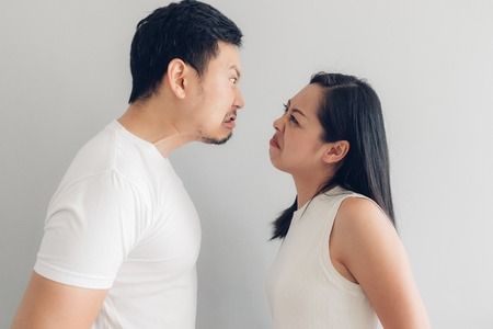 Photo for Angry Asian couple lover in white t-shirt and grey background. - Royalty Free Image