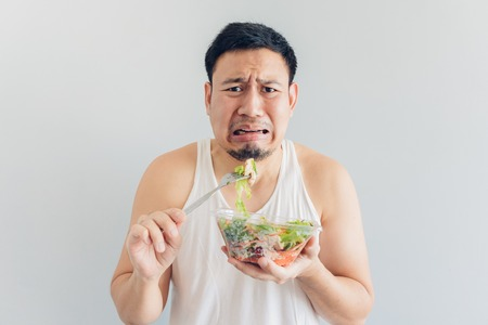 Photo pour Asian man hates healthy salad meal. - image libre de droit