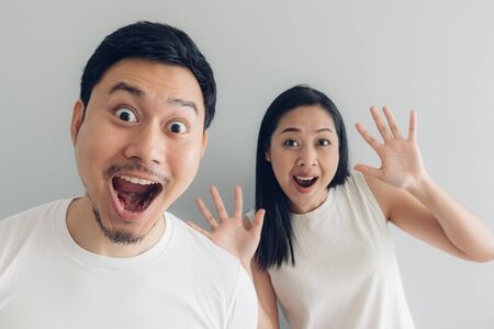 Foto de Surprised and shocked Asian couple lover in white t-shirt and grey background. - Imagen libre de derechos