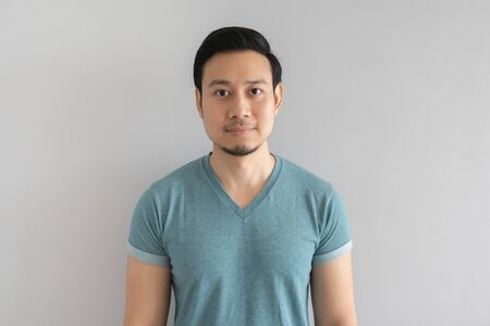 Foto de Normal straight face portrait of Asian man in blue t-shirt on grey background. - Imagen libre de derechos