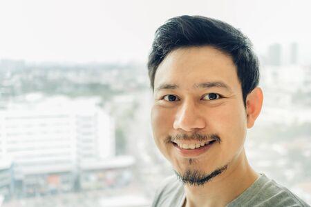 Photo pour Happy Asian man selfie in his condominium room. - image libre de droit