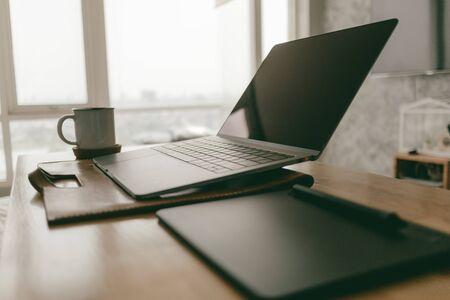 Foto de Work from home minimal creative items set of a laptop and pen tablet in the apartment. - Imagen libre de derechos