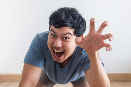 Photo for Funny and playful teasing of Asian man acts like a beast roar. - Royalty Free Image