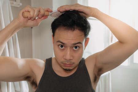 Photo pour Asian man is combing his hair in the bathroom. - image libre de droit