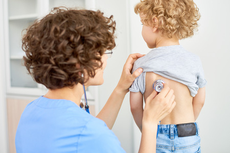 Photo pour Portrait of female doctor listening to childs breathing from the back using stethoscope to check for symptoms of bronchitis or pneumonia - image libre de droit