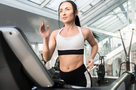Photo pour Young Woman Running on Treadmill - image libre de droit