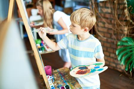 Photo pour Cute Boy Painting in Art Class - image libre de droit