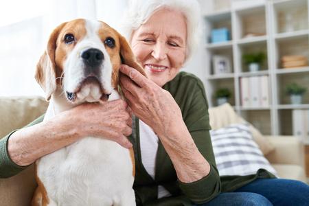 Photo pour Happy Senior Woman Hugging Dog - image libre de droit
