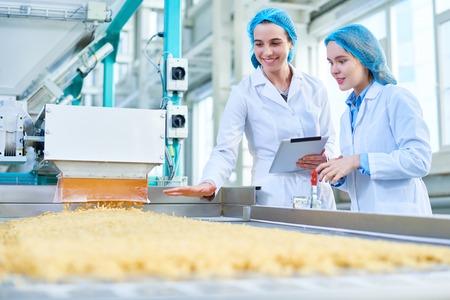 Photo pour Young Women Working at Food Factory - image libre de droit