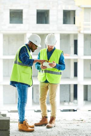 Photo pour Busy coworkers discussing plan of construction work - image libre de droit