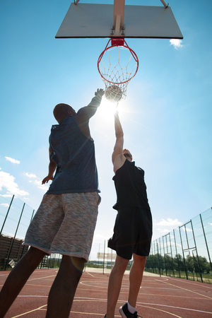 Two Active Men Playing Basketball Outdoors