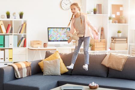 Photo pour Funny Girl Jumping on Sofa - image libre de droit