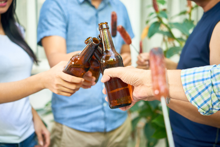Photo pour Hands of friends toasting with beer bottles when having party in backyard - image libre de droit