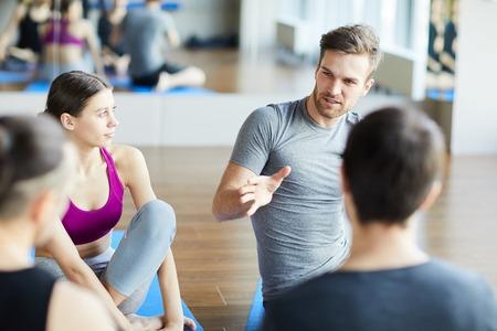 Photo pour Sporty guy sharing ideas at yoga class - image libre de droit