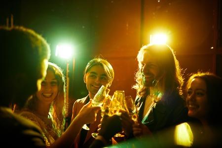 Photo pour Hilarious friends drinking champagne at party - image libre de droit