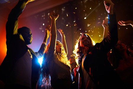 Photo pour Excited people dancing at concert in nightclub - image libre de droit
