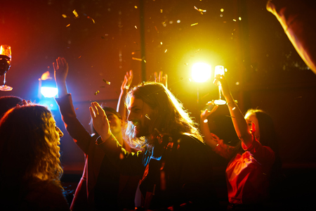 Photo pour Excited people dancing under confetti - image libre de droit