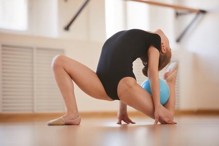 Photo pour Full length portrait of flexible girl doing gymnastics with ball in studio lit by sunlight, copy space - image libre de droit