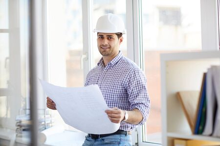 Photo pour Smiling Middle-Eastern Engineer Holding Plans - image libre de droit