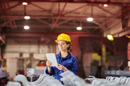 Photo pour Smiling Woman Using Digital Tablet at Factory - image libre de droit